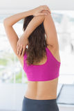 Rear view of a sporty woman stretching hands at yoga class Royalty Free Stock Photos