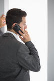 Rear view of stern businessman standing in front of window phoning Royalty Free Stock Image
