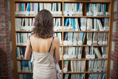 Rear view of a student at bookshelf in the library Stock Image