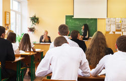 Rear view of students listening to female student near the desk stock image