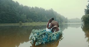 Rear view of the stylish couple in vintage sloth floating on romantic boat decorated with green herbs along the foggy