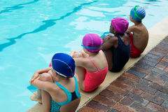 Rear view of swimmers sitting at poolside Stock Photo