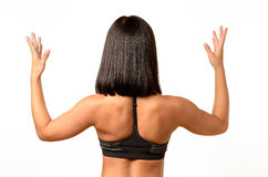 Rear view of a tanned woman with raised arms Stock Photography