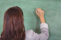 Rear view of teacher writing on chalkboard in a classroom Stock Photo