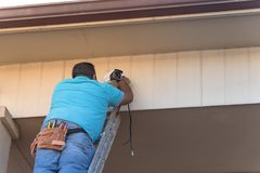 Rear view of technician installing surveillance camera on roof. Latino handyman on ladder with tool belt  installing CCTV Royalty Free Stock Photo