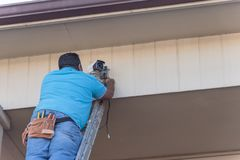 Rear view of technician installing surveillance camera on roof. Vintage tone rear view of technician installing surveillance camera on roof. Latino handyman on Royalty Free Stock Photography