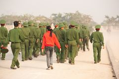 Rear view, Teen girl in red shirt walking with a group of Young Vietnamese soldier on the street, during site visit program. Dien stock images