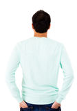 Rear view of teen guy in casuals with his hands in back jeans pockets Royalty Free Stock Photos