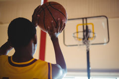 Rear view of teenage boy playing basketball. In court Royalty Free Stock Images