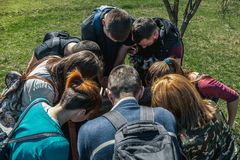 Rear view of teenage boys and girls carrying backpacks and looking down into the well. stock images