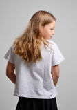 Rear view of the teenage girl concealing something. A blonde girl is hiding something. She is standing back and looking out of the corner of her eye on the gray Stock Image