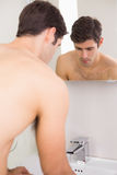Rear view of tensed shirtless man at washbasin Royalty Free Stock Images