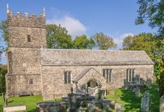 Rear view of the church at Parracombe, Devon. Rear view of the 13th century church of Saint Petrock in Parracombe, Devon showing old graves in shade in the stock image