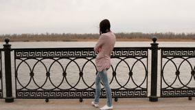 Rear View of a Thoughtful Casual Young Woman Weared Jeans and Jacket Facing at the River 4K stock footage