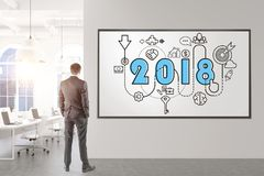 Thoughtful businessman 2018 business plan rear. Rear view of a thoughtful fair hair businessman wearing a suit and thinking. He is looking at a 2018 sketch on an Stock Photo