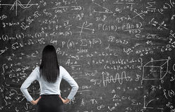 Rear view of a thoughtful woman who tries to solve math problems. Math calculations on black chalk board Stock Photography