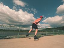 Rear view to inline skater in red t-shirt and black pants skating on the bridge . Outdoor inline skating Royalty Free Stock Images