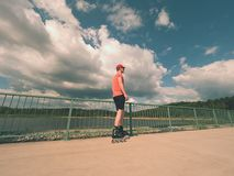 Rear view to inline skater in red t-shirt and black pants skating on the bridge . Outdoor inline skating Stock Images