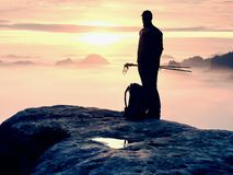 Rear view to  traveler stand alone on cliff with mist bellow legs,  sunshine in cloudy sky Stock Images