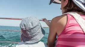 Rear view of toddler son with his mother on boat deck. During cruise on sunny day Royalty Free Stock Photo