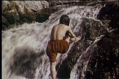 Rear view of topless Native American woman bathing in stream stock video footage