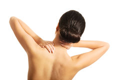 Rear view of topless woman with neck pain Royalty Free Stock Image