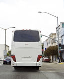 Rear View Tour Bus. Rear view of charter tour bus in city traffic. Vertical Royalty Free Stock Images