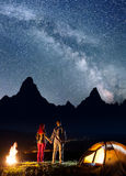 Rear view tourist couple - girl and guy holding hands, standing near camp and bonfire, enjoying starry sky Royalty Free Stock Photos