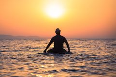 Silhouette of man sitting on surfboard at sunset over sea. Rear view of tourist guy with hat sitting on surfboard in ocean at sunset Stock Photo
