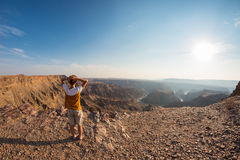 Rear view of tourist looking at expansive view over the Fish River Canyon, scenic travel destination in Southern Namibia. Ultra wi Stock Photography