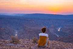 Rear view of tourist looking at expansive view over the Fish River Canyon, scenic travel destination in Southern Namibia. Ultra wi Stock Images