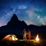Rear view tourist pair holding hands, standing near tent and campfire, enjoying incredibly beautiful starry sky Stock Photo