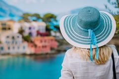 Rear view of tourist woman wear blue sunhat and white clothes admire view of colorful tranquil colorful houses of Assos royalty free stock photos