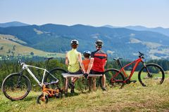 Rear view of tourists, mom, dad and child sitting on wooden bench, resting after cycling bicycles Stock Photography