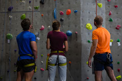 Rear view of trainer with athletes standing by climbing wall. At gym Royalty Free Stock Images