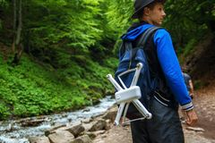 Rear view of a traveler with backpacks and a copter stands in front of a waterfall. royalty free stock images