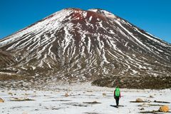Rear view of the traveler and mountain tramper walking towards the Mount Ngauruhoe active volcano and caring the backpack royalty free stock photography