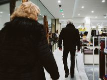Rear view of trendy senior couple walking in Printemps luxury de Royalty Free Stock Photography