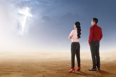Rear view of two asian business people standing on desert and looking at glowing christian cross. On the sky royalty free stock photos