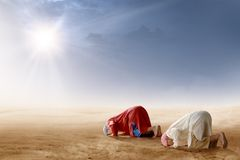 Rear view of two asian muslim man praying in prostration position on desert stock images
