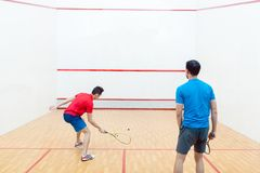 Rear view of two competitive young men playing squash game royalty free stock photo