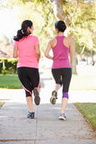 Rear View Of Two Female Runners On Suburban Street Royalty Free Stock Images