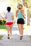 Rear View Of Two Female Runners On Suburban Street Stock Image