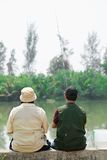 In wait. Rear view of two fishers waiting for fish Royalty Free Stock Images