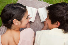 Rear view of two friends looking at each other. While reading a book in a park Stock Image