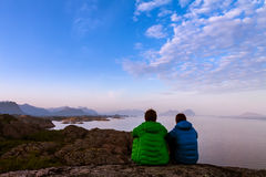 Rear view of two friends sitting together on clief. Near ocean, midnight sun time, Lofoten island, Norway Stock Photo
