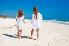 Rear view of two little sisters in white clothes Stock Images