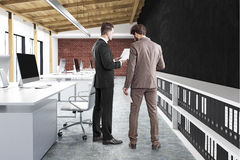 Rear view of two men in office, black wall. Rear view of two businessmen standing in an office with many tables. There are computers on them and white shelves Stock Photo