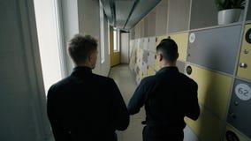 Rear view of two men talking, walking along corridor indoors. Rear view of two men talking, walking along corridor indoors, young male colleagues communicates stock video