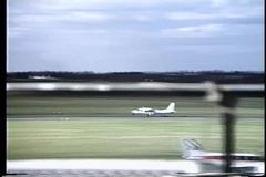 Rear view two men watching propeller plane take off stock footage